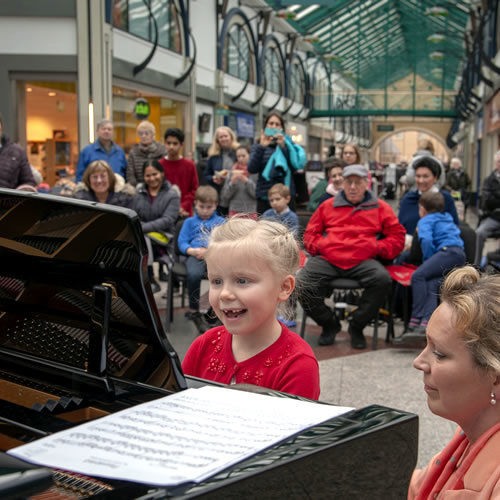 Child playing piano in public